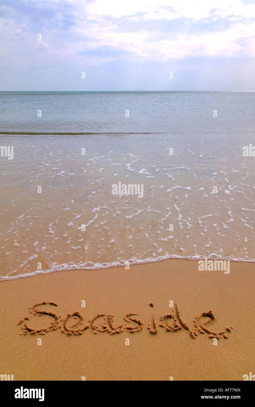Seaside written in sand on a beach - Stock Image