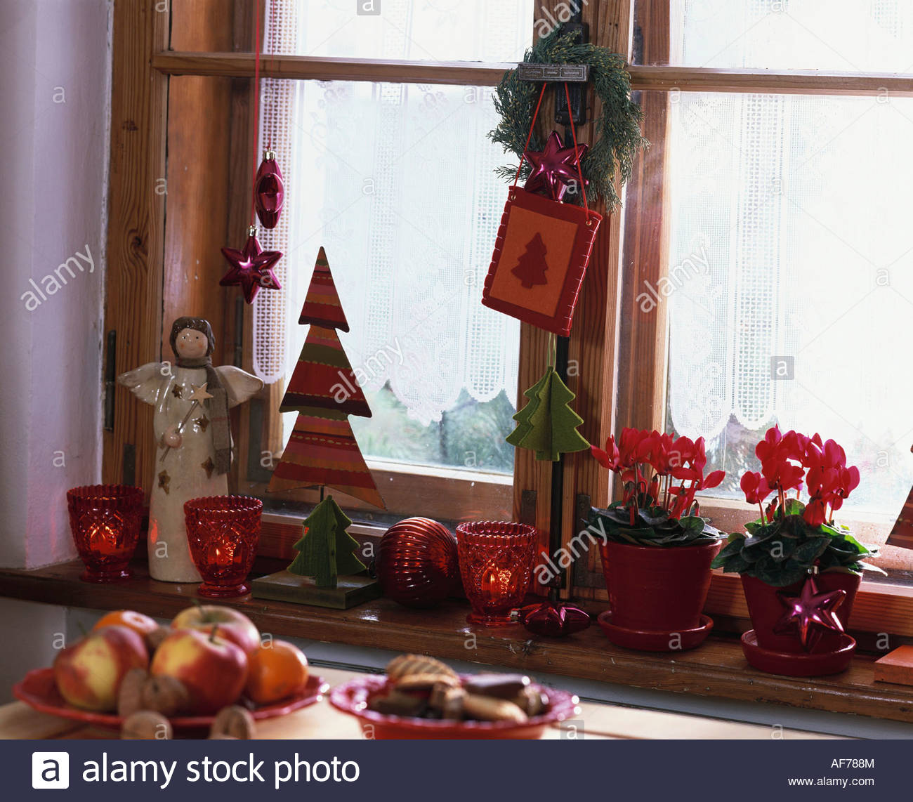 cyclamen on window sill with christmas decorations stock image