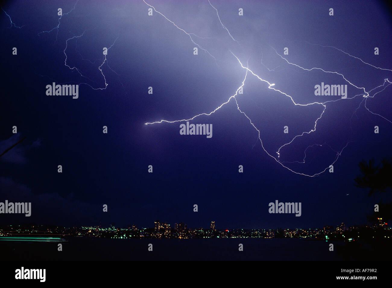 Sheet lightning over Sydney city suburb waterfront at night. - Stock Image