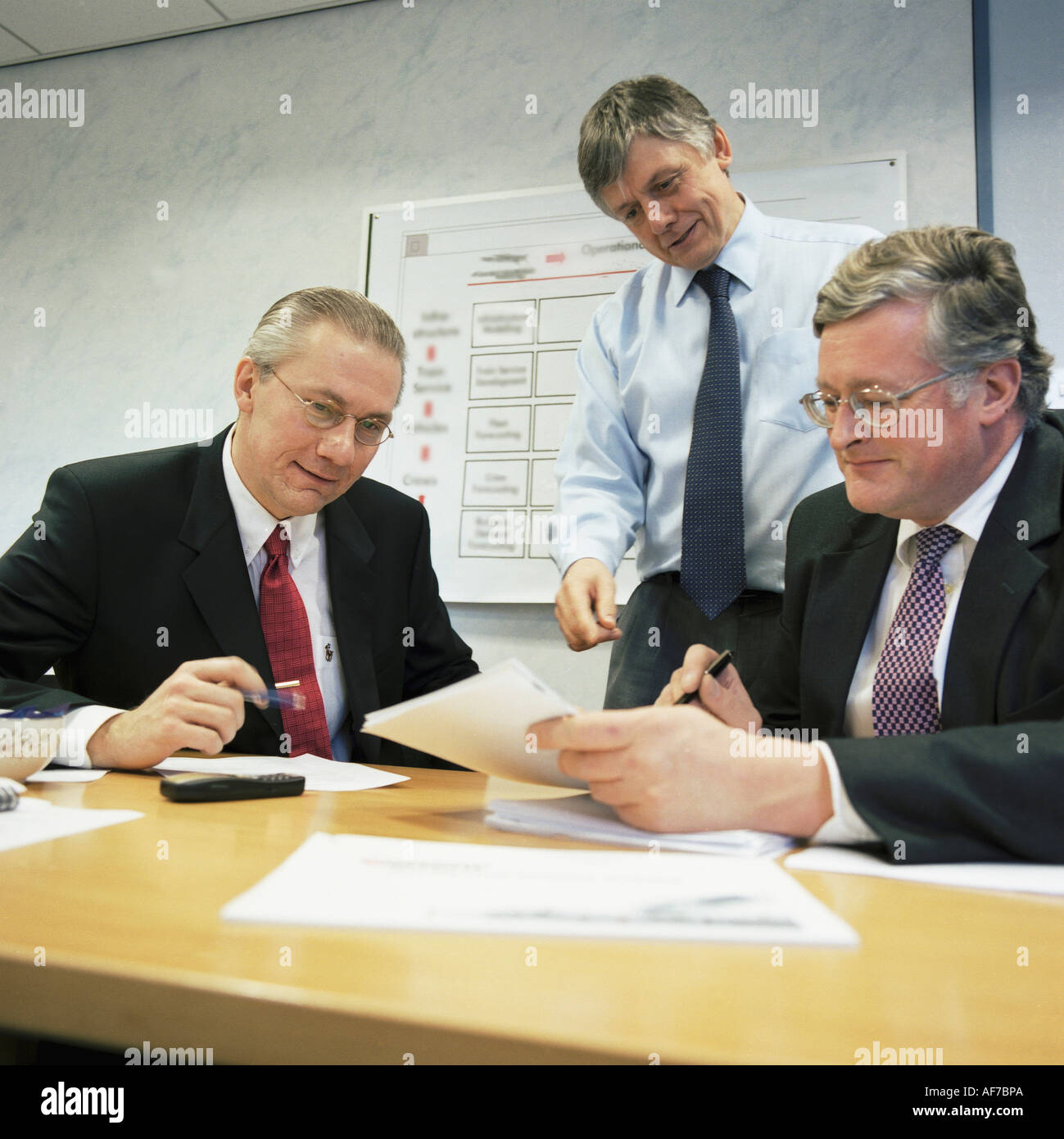 British industry. Three businessmen meeting in office. - Stock Image