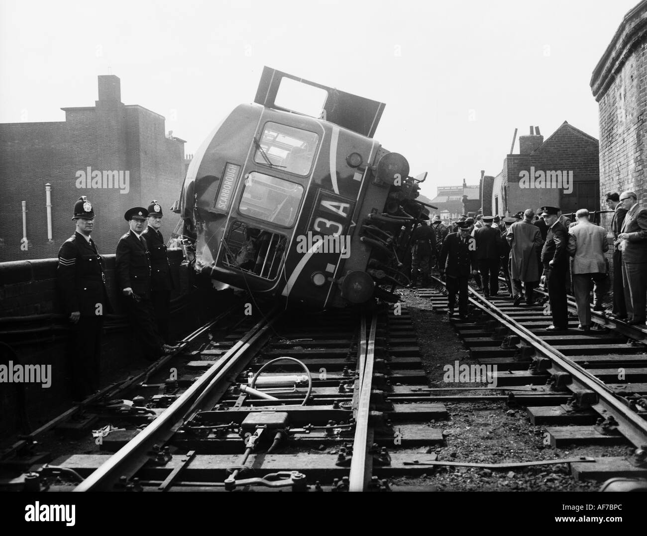 Vintage black and white photograph of a crowd of people including police viewing derailed railway locomotive tipped on its side. - Stock Image