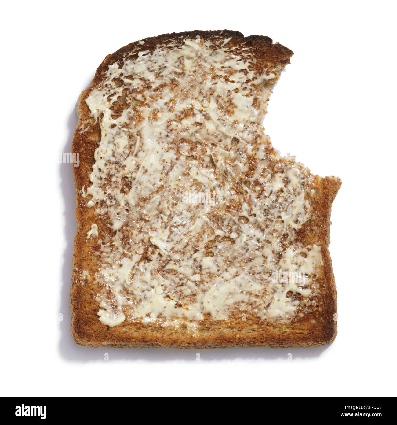 A bitten slice of buttered toast - Stock Image