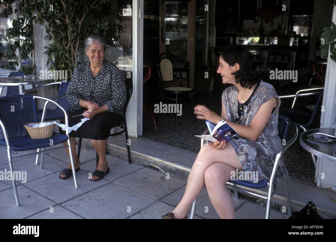 Tourist Visitor to Crete practices her Greek language with a local who is lace making in a Cafe Southern Crete Greece - Stock Image