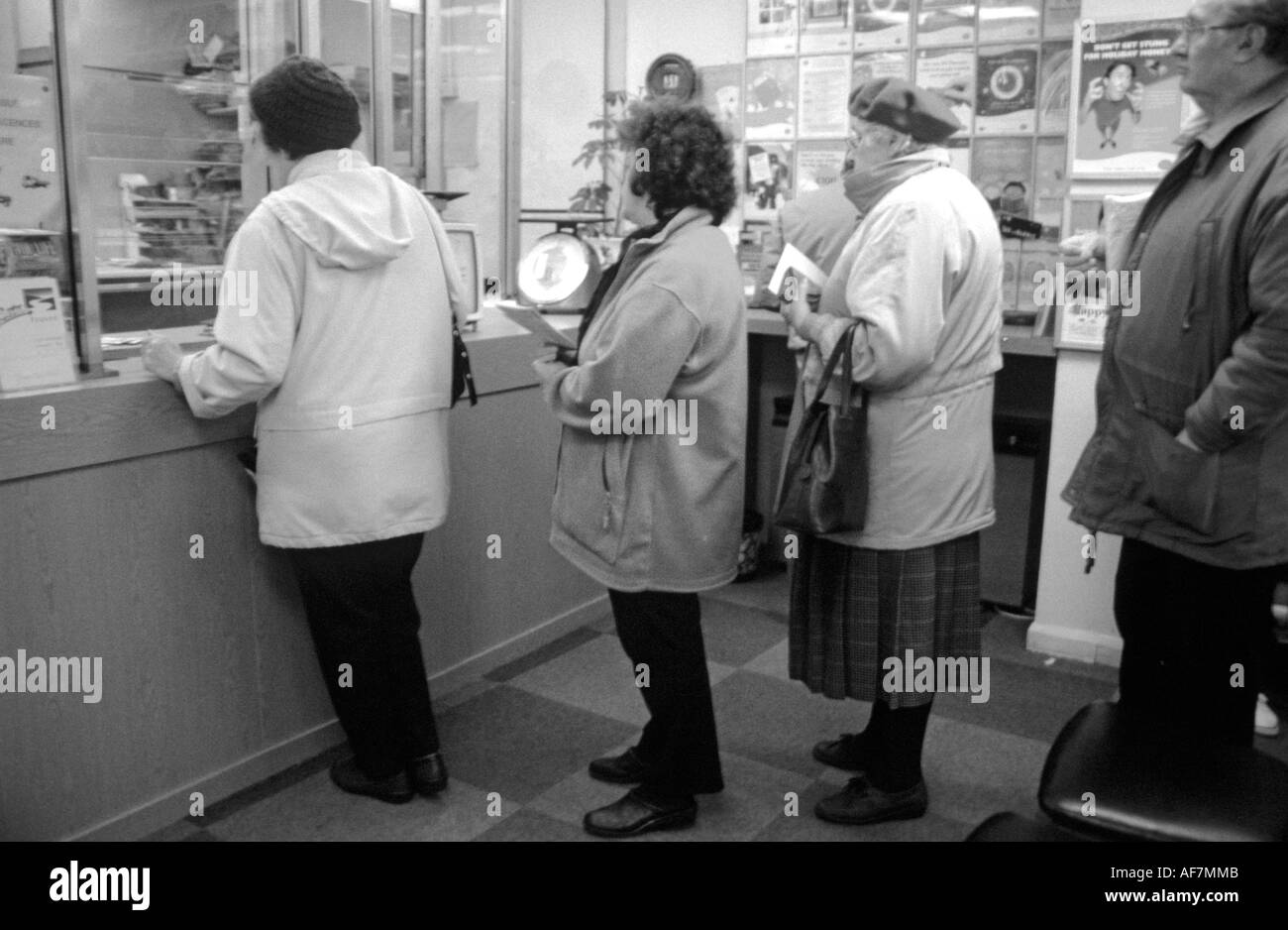 elderly people queueing in rural sub post office threatened for closure - Stock Image