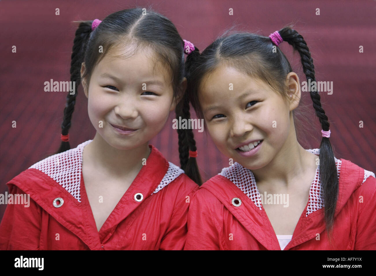 Young twin girls with pony tail Yichang Hubei China - Stock Image