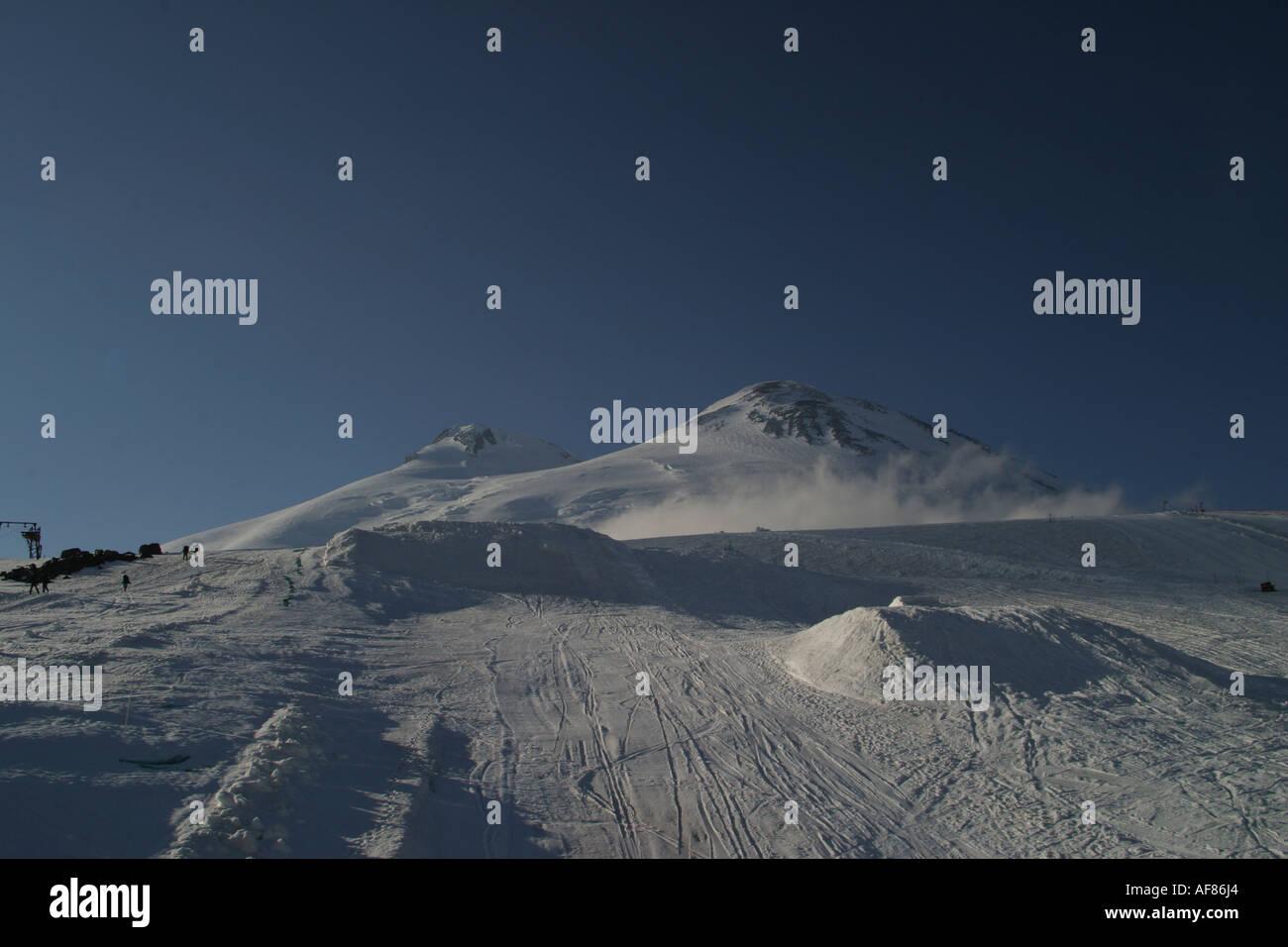Mountains landscape 22 - Evening Elbrus in pure blue sky and snowboard big-airs, Caucasus, Elbrus region, Kabardino-Balkari - Stock Image