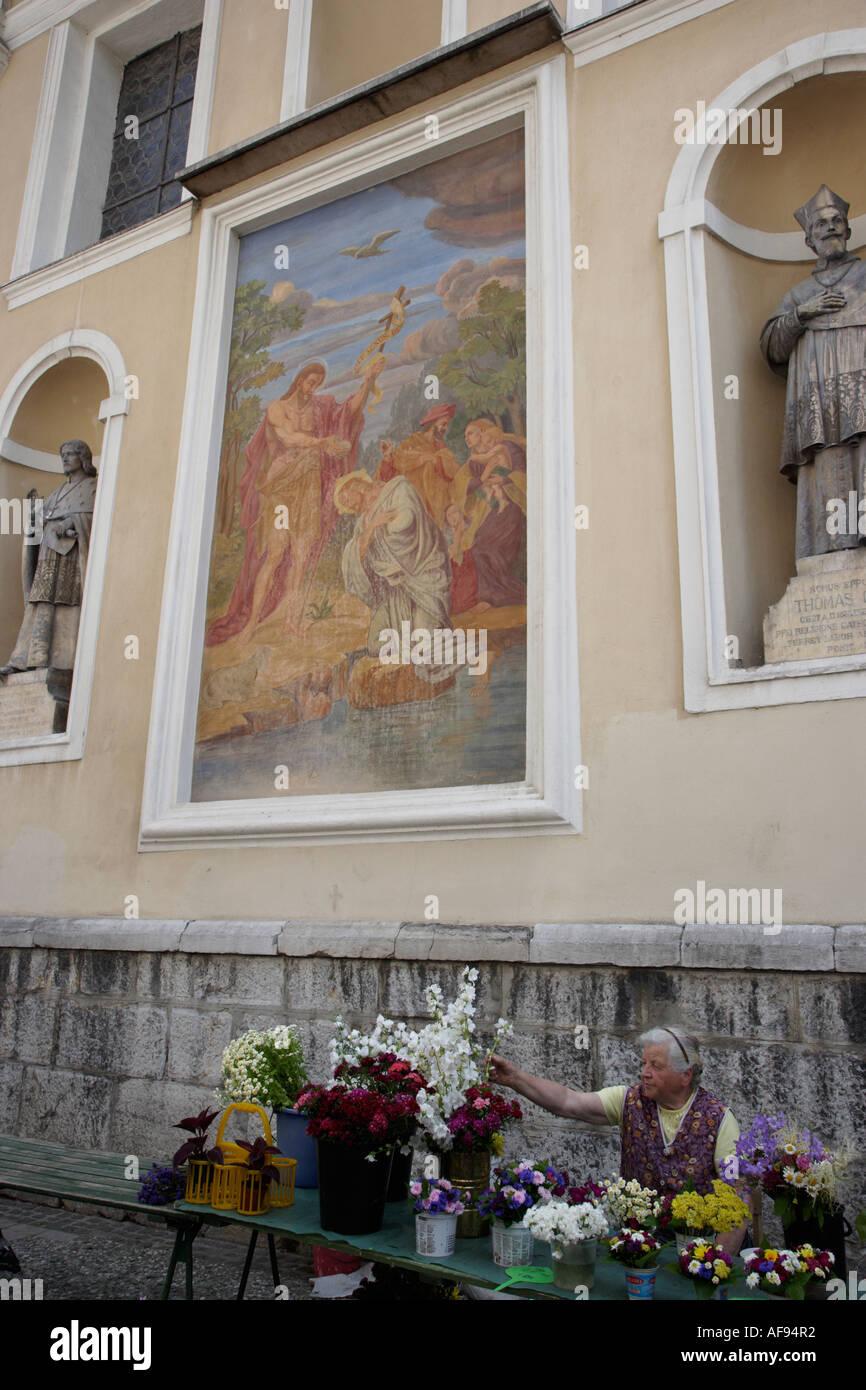 Slovenia Ljubljana Vlodnik Square Elderly Lady selling flowers at the rear of Saint Nicholas Cathedral - Stock Image