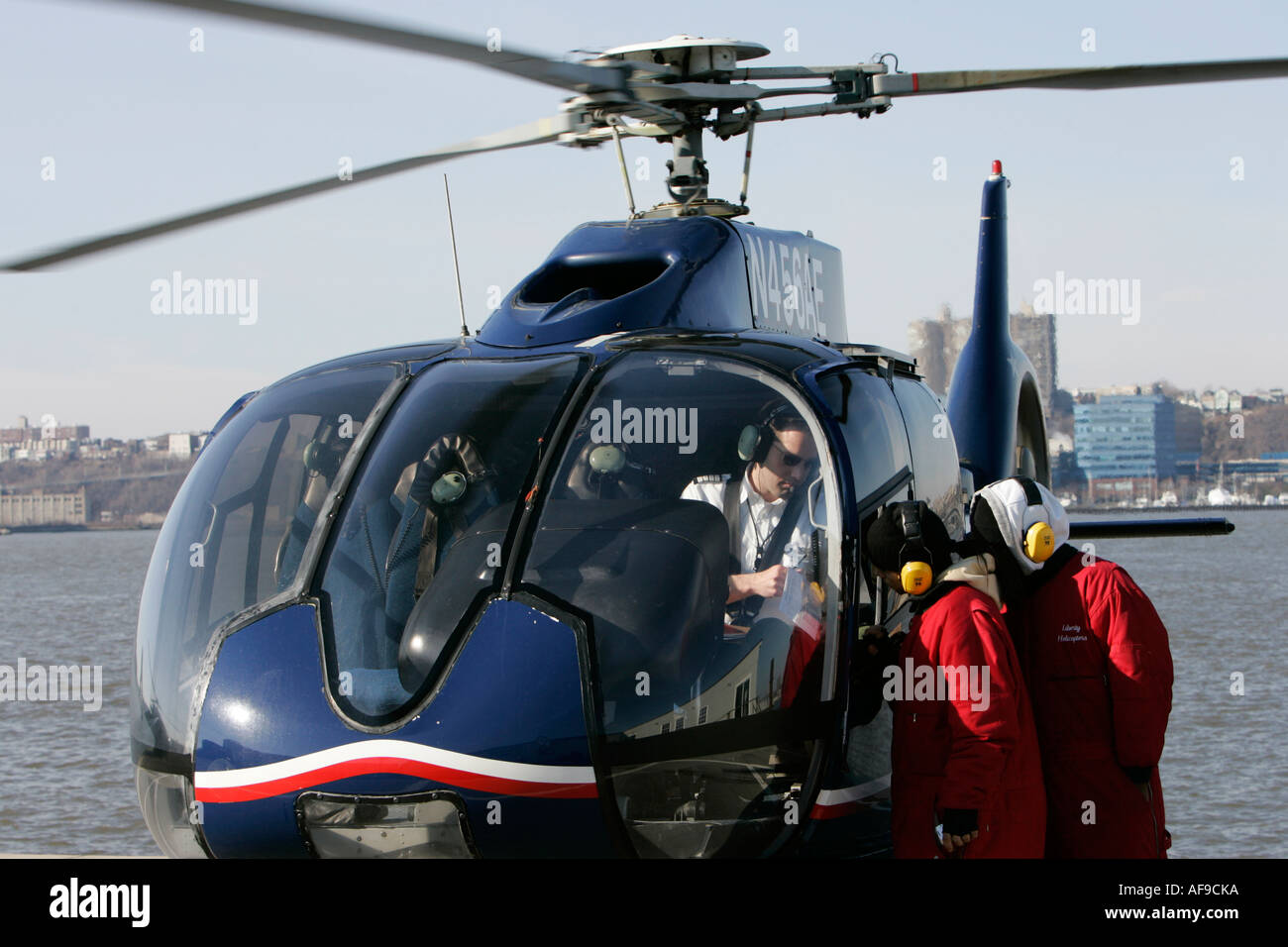 EC130 american eurocopter pilot checks with two members of ground crew at liberty helicopters sightseeing tours - Stock Image