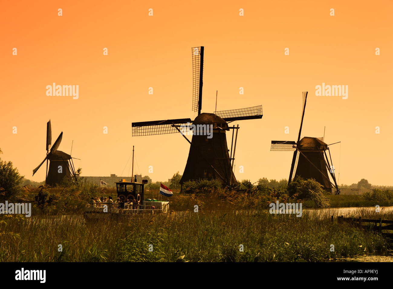 Tourist on a sightseeing cruise boat at sunset viewing the windmills at Kinderdijk, Holland - a UNESCO World Heritage - Stock Image