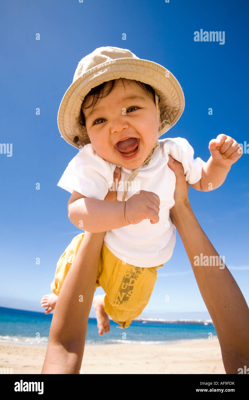 Hands holding baby (6-9 months) into air, portrait - Stock Image