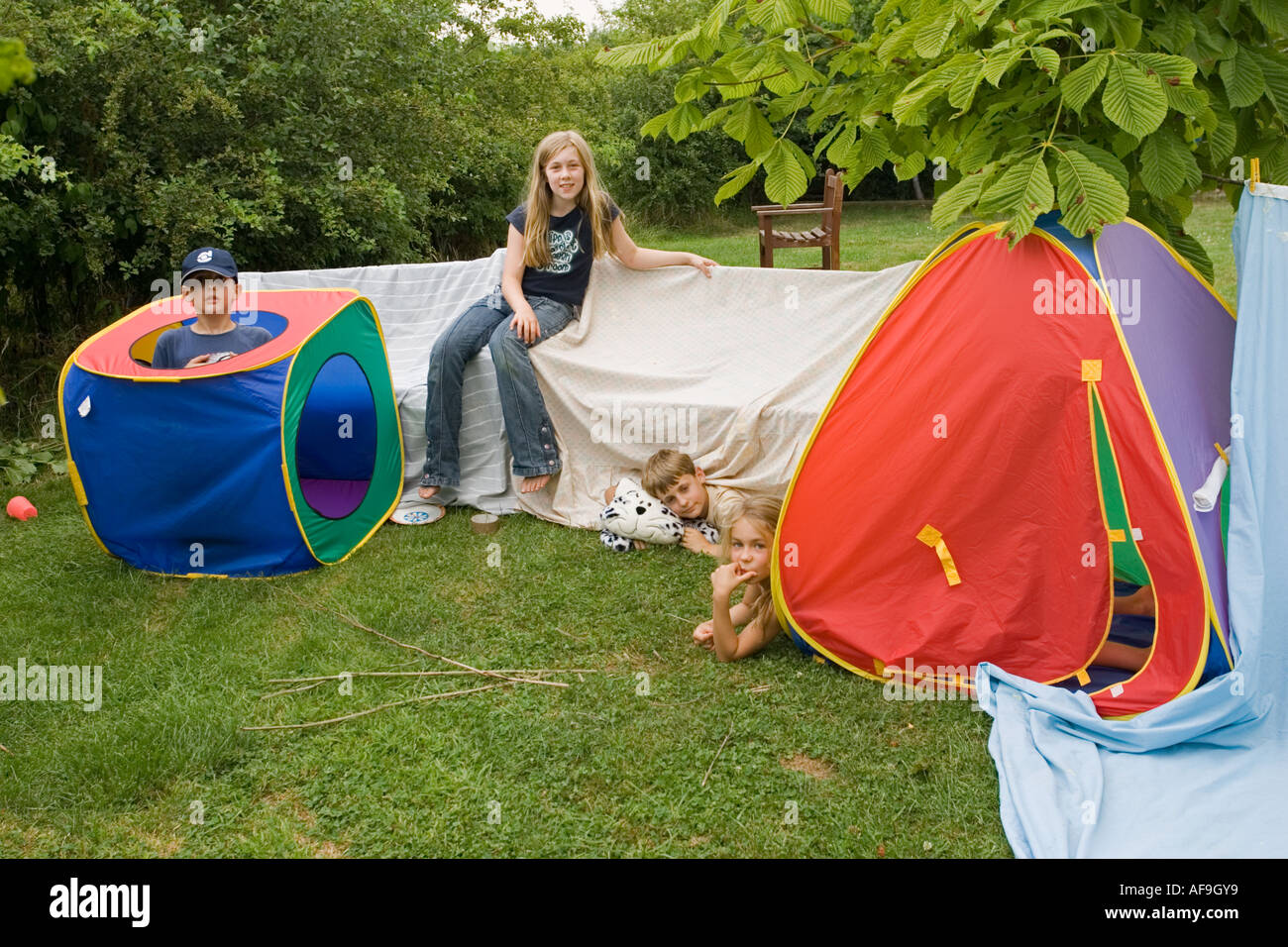 Children aged 9 12 playing outside in pretend houses made from blankets and tents in garden Cotswolds UK - Stock Image