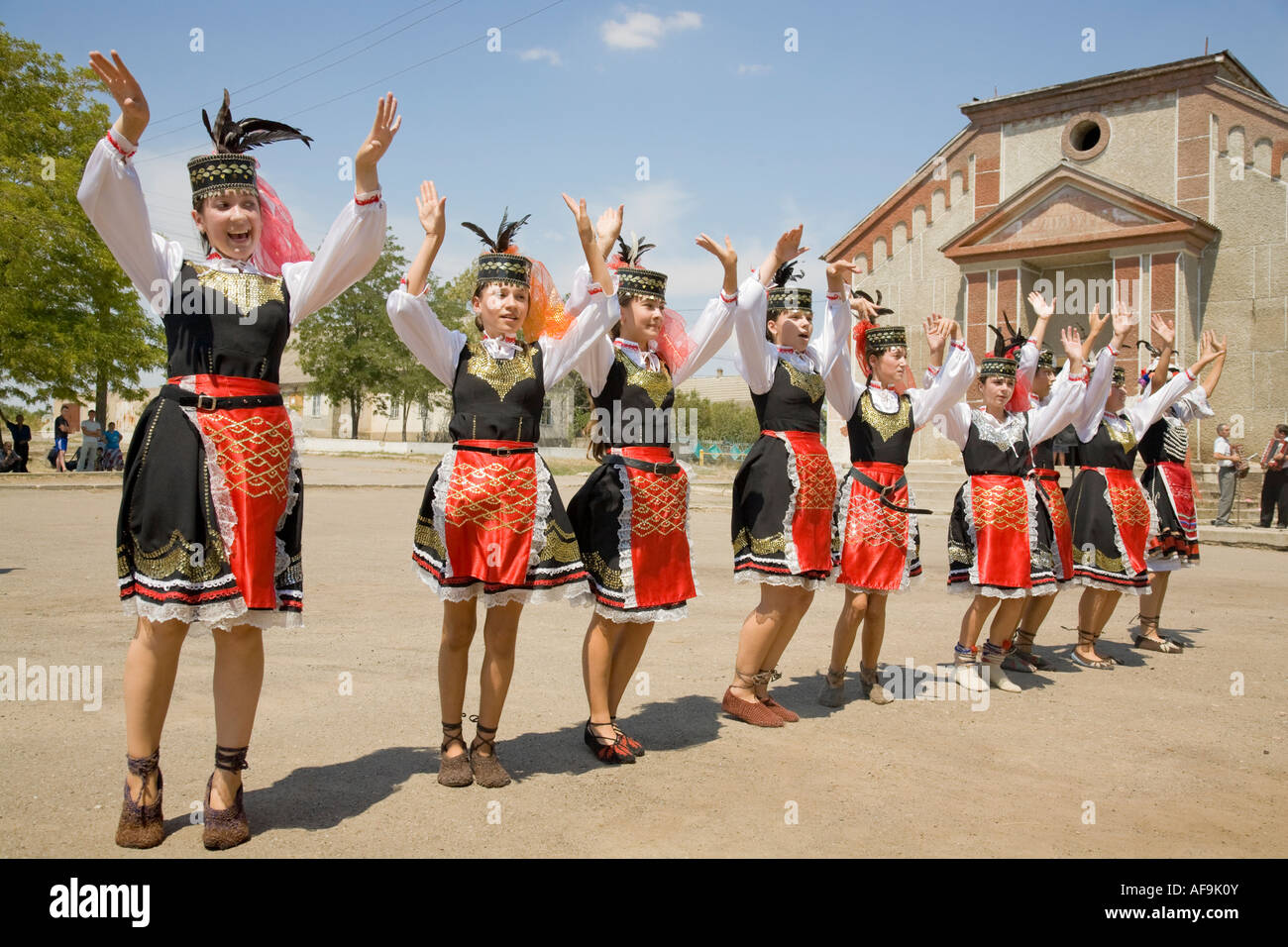 Young girls in traditional Ukrainian costumes dancing in front of the town house in Plotzk / Ukraine Stock Photo