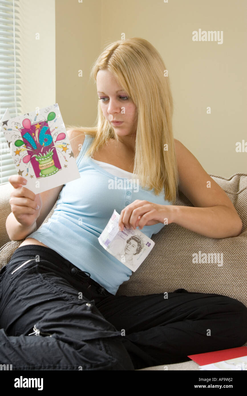 A Teenage Girl Reading Birthday Card At Becoming 16 Years Old With 20 Note As Gift