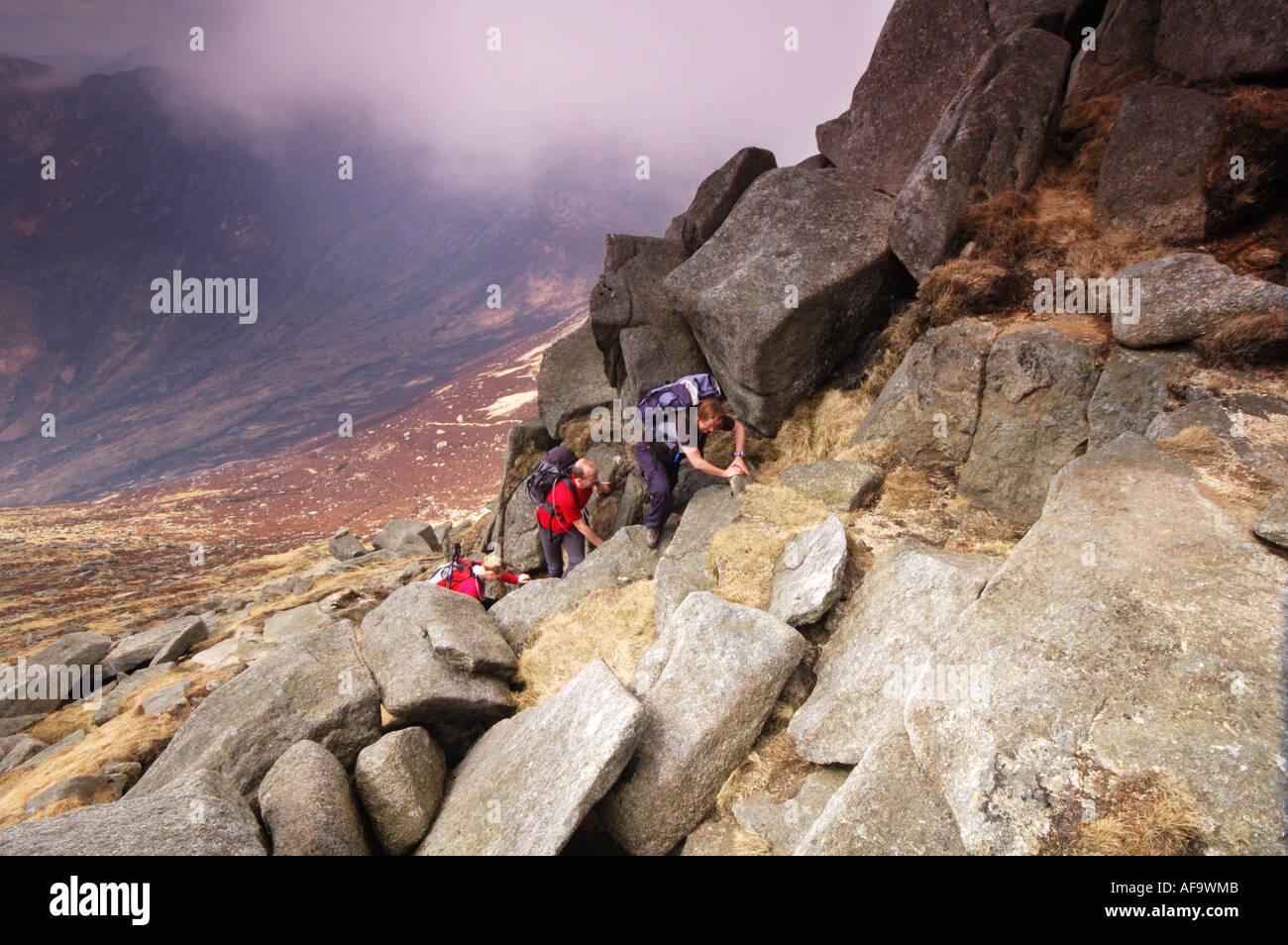 Walkers scrambling on North Goatfell, Isle of Arran, Scotland female - Stock Image