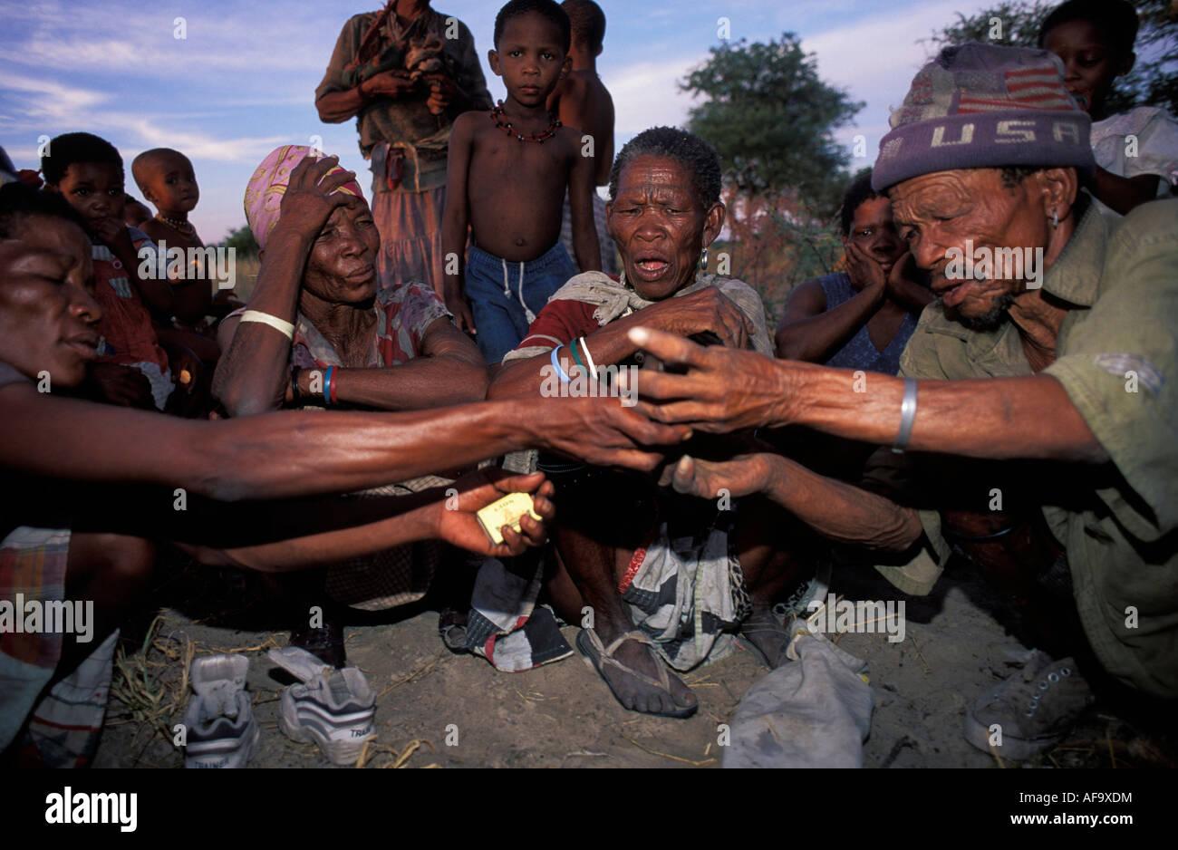 Old Kua bushman people smoking pipe, Molapo, Central Kalahari Game Reserve; Botswana - Stock Image