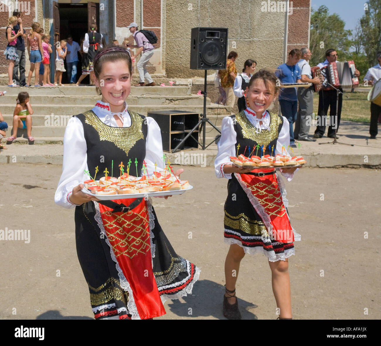 Two young girls in traditional Ukrainian costumes serving canapes in Plotzk / Ukraine Stock Photo
