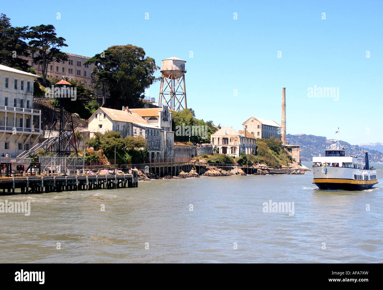 A San Francisco Bay tour boat sailing by the old prison buildings on Alcatraz Island - Stock Image