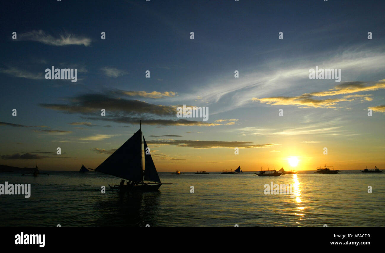 Sailboats off of White beach at sunset in Boracay, Philippines. Stock Photo