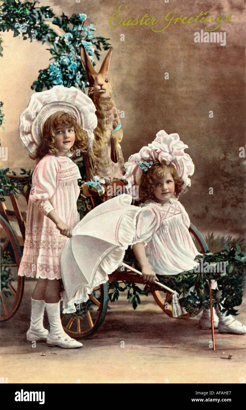 Early 1900s Easter greetings postcard depicting two young girls pushing a cart. Circa 1905 U.K. - Stock Image