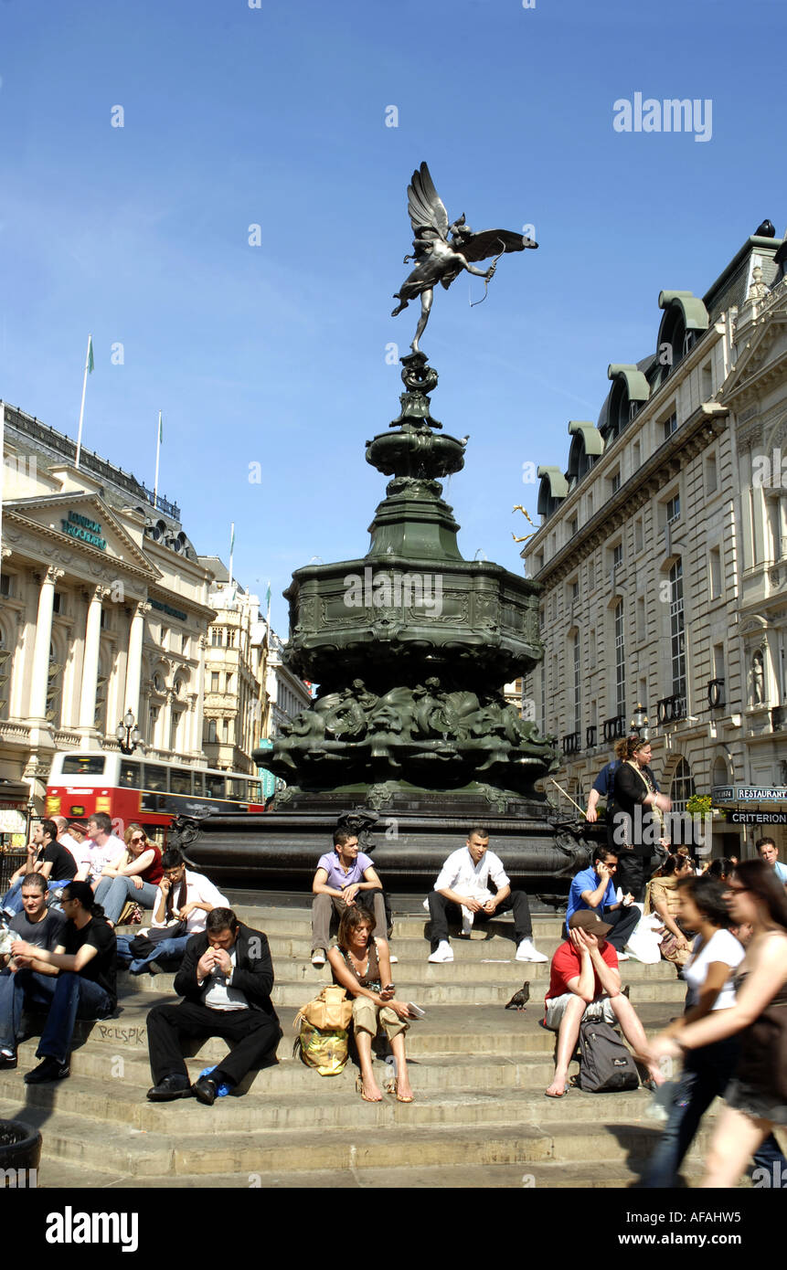 Tourists sitting on the steps around the  Bronze Statue Of  Eros, Piccadilly Cicus, London, England. Monument erected 1893 - Stock Image