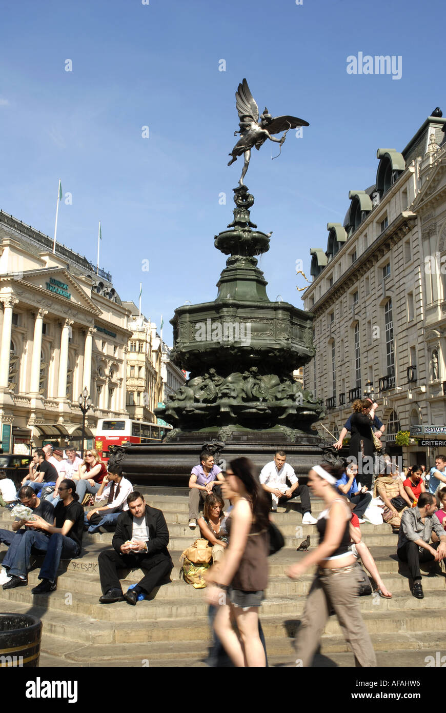 Tourists sitting on the steps around the  Bronze Statue Of  Eros, Piccadilly Circus, London, England. Monument erected 1893 - Stock Image
