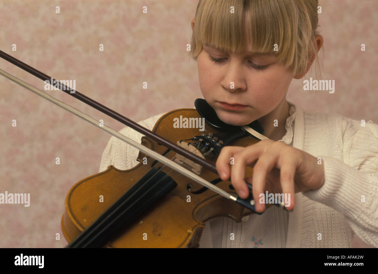 girl playing violin with her left hand - Stock Image