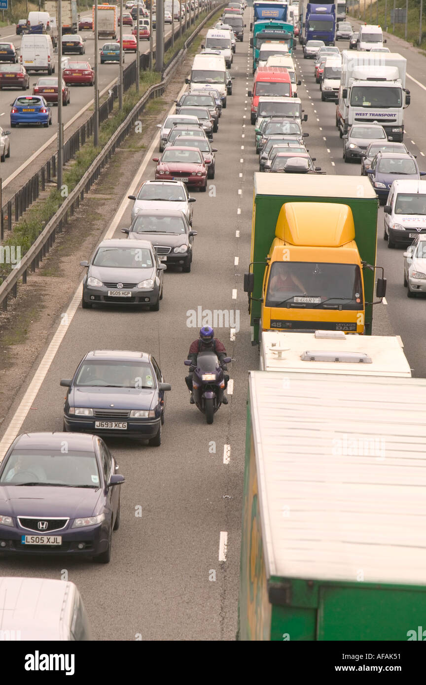 traffic congestion on the M1 motorway at loughborough due to sheer volume of traffic with a motorbike riding between lanes - Stock Image