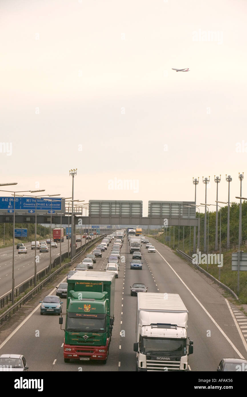 a plane takes off from East Midlands Airport near Loughborough over a congested M1 motorway - Stock Image