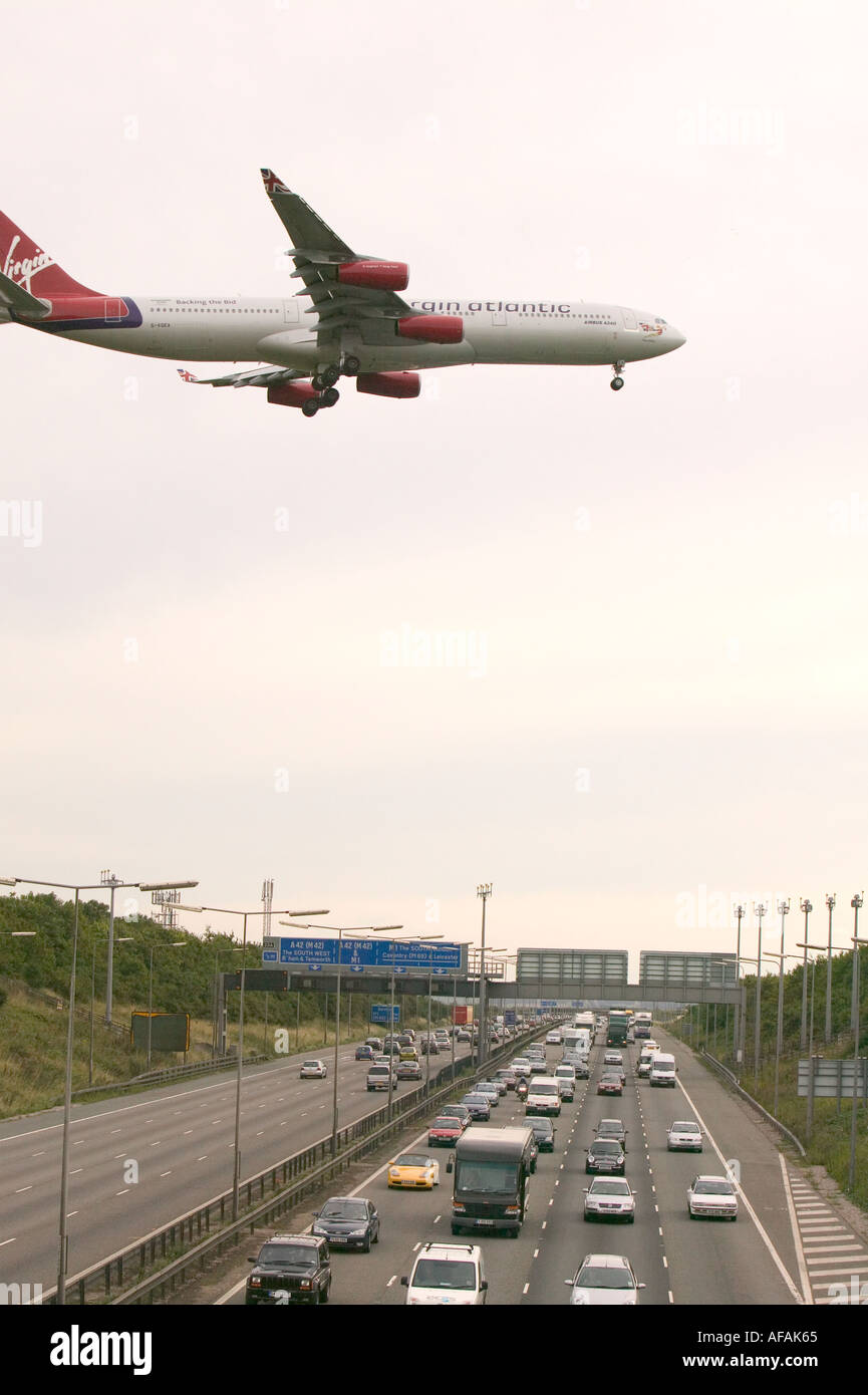 a plane coming in to land at East midlands airport flying low over a congested M1 motorway - Stock Image