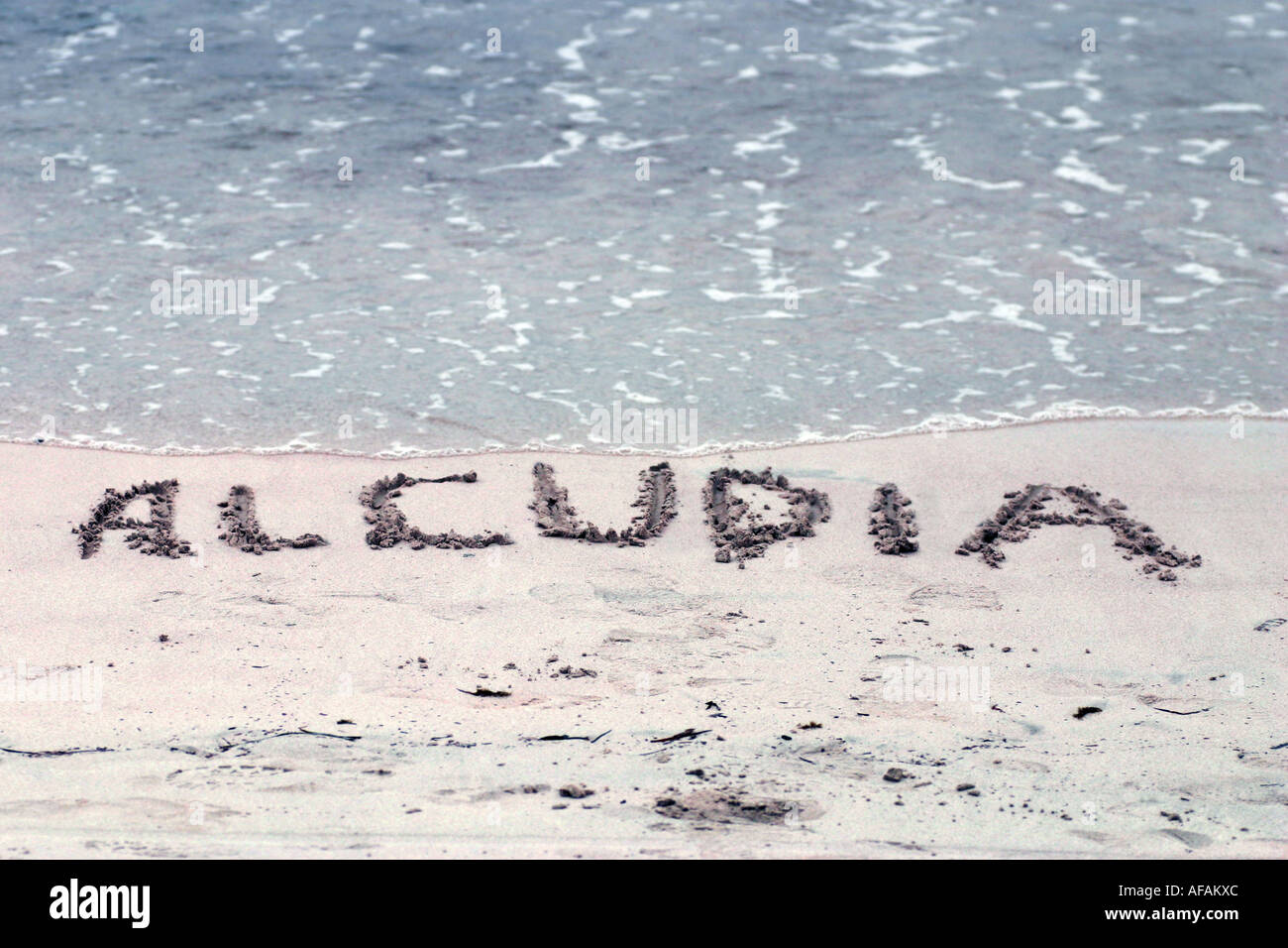 The word ALCUDIA is written in the sand by the sea in Alcudia Mallorca Spain - Stock Image