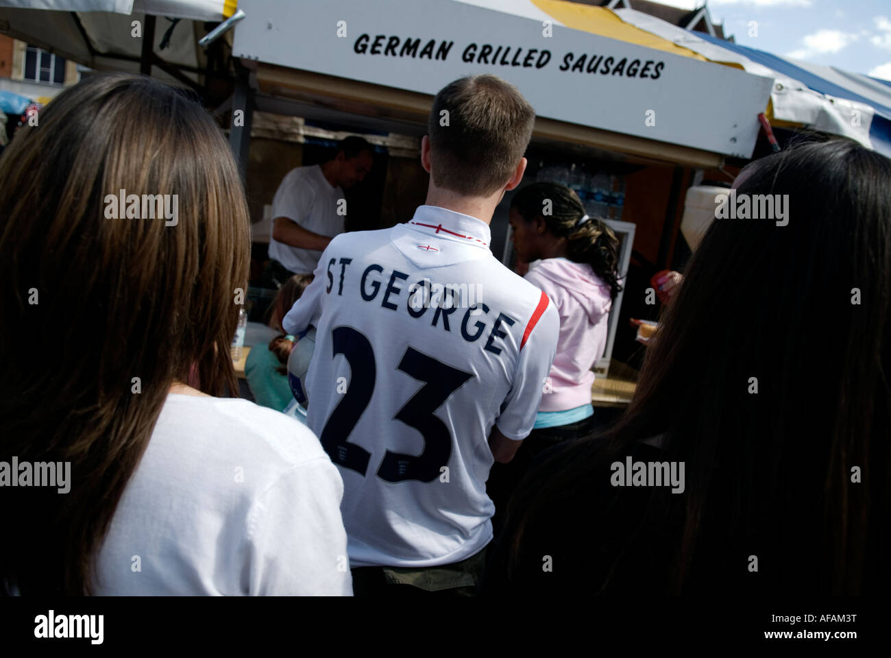 37745c852 MAN WEARING A PATRIOTIC ENGLAND SHIRT SHOWING ST GEORGES DAY DATE BUYING A  SAUSAGE FROM A