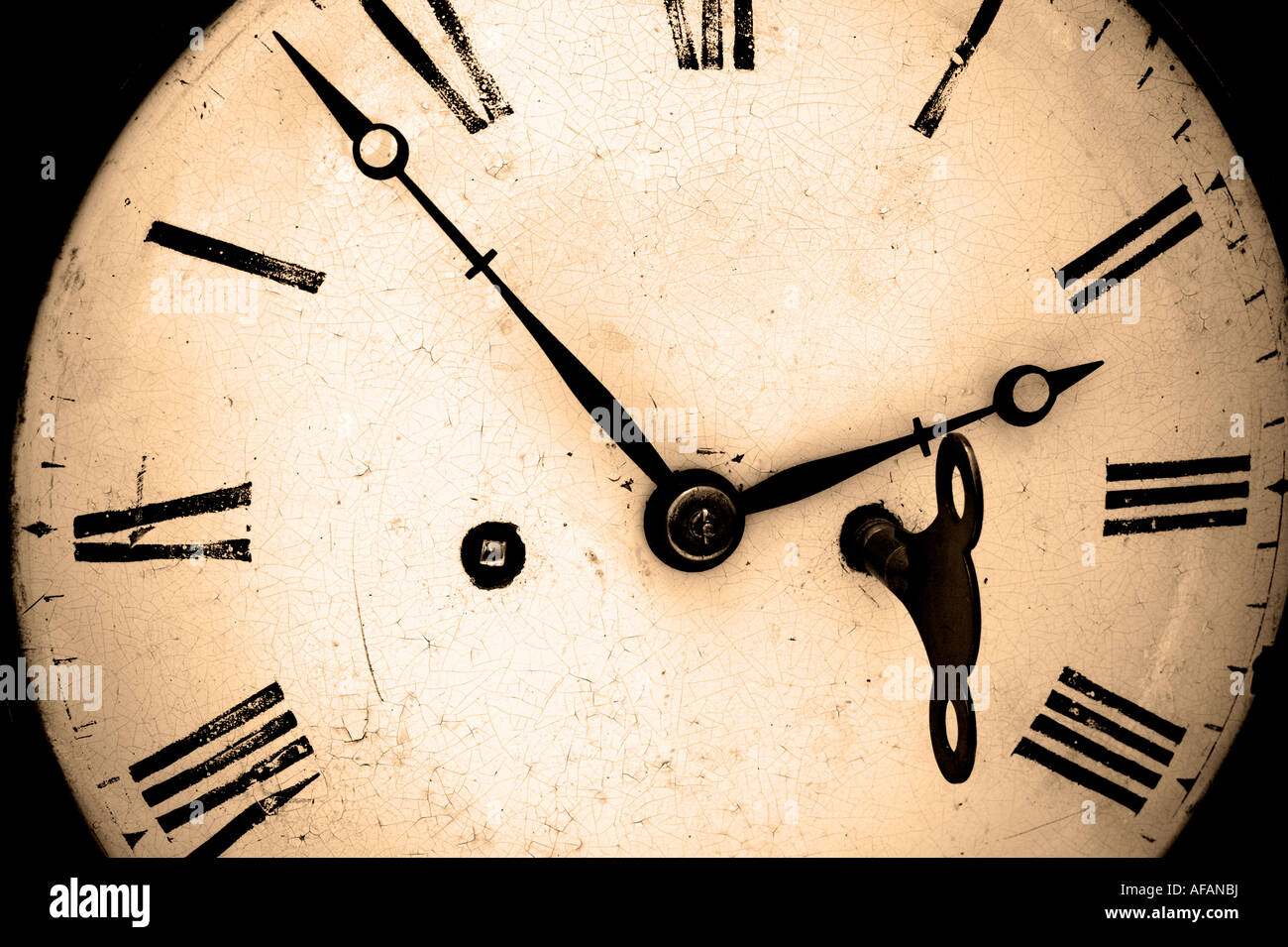 Antique clock face with winder key in position sepia toned - Stock Image
