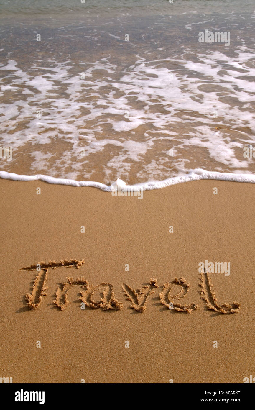 Travel written in the sand on a beach Stock Photo