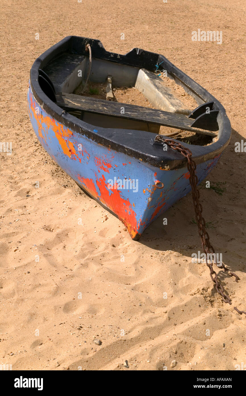 Old boat with peeling paint abandoned on the sand - Stock Image