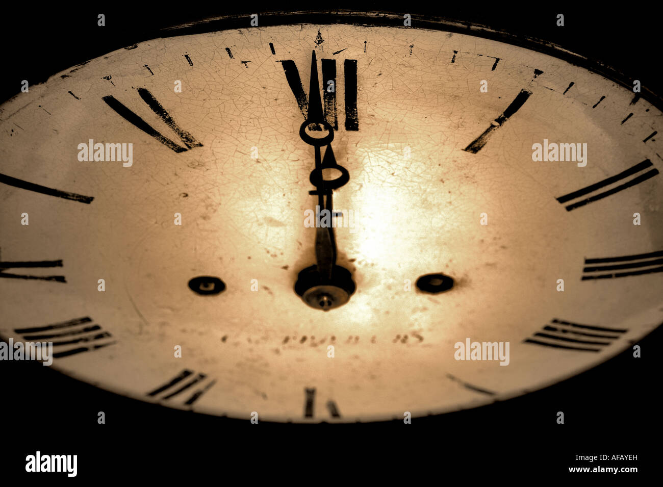Antique clock face with the hands at 12 o clock dark and grainy sepia toned image - Stock Image