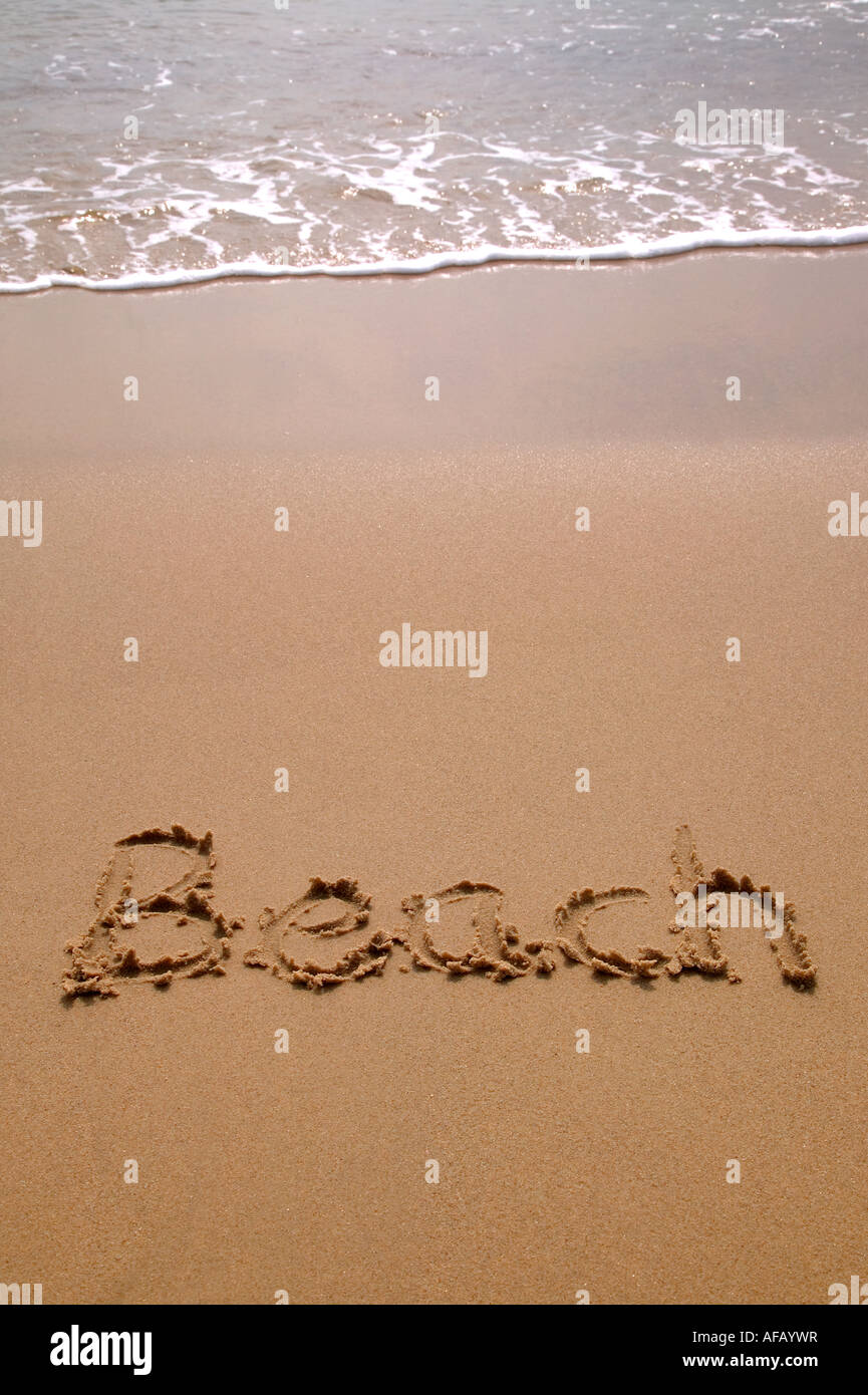 Beach written in sand at the beach - Stock Image