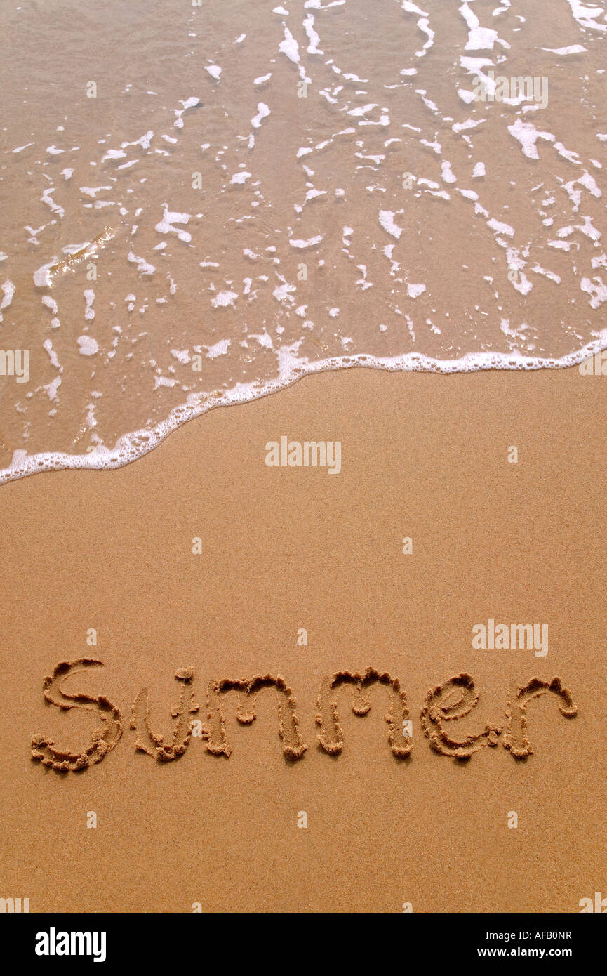 Summer written in sand at the beach - Stock Image