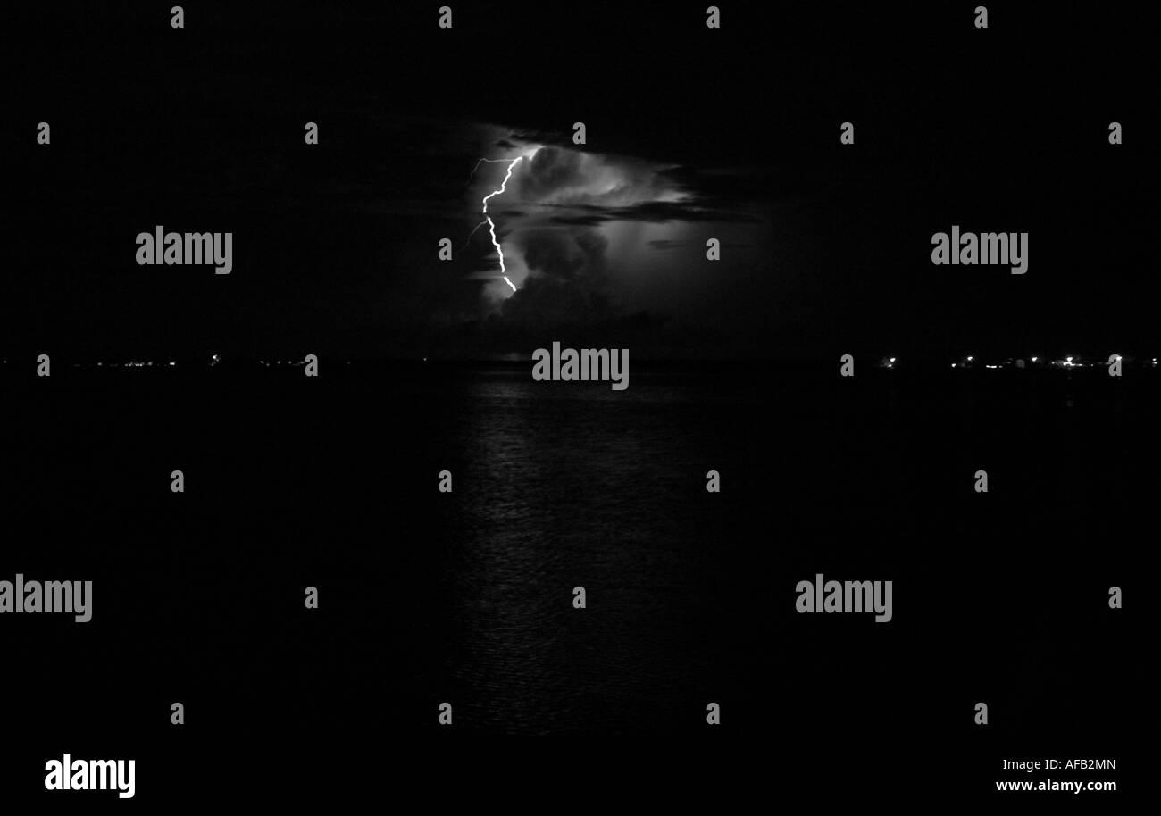 monochrome Lightning penetrating the clouds illuminating the night-time sea, Utila, Honduras Stock Photo