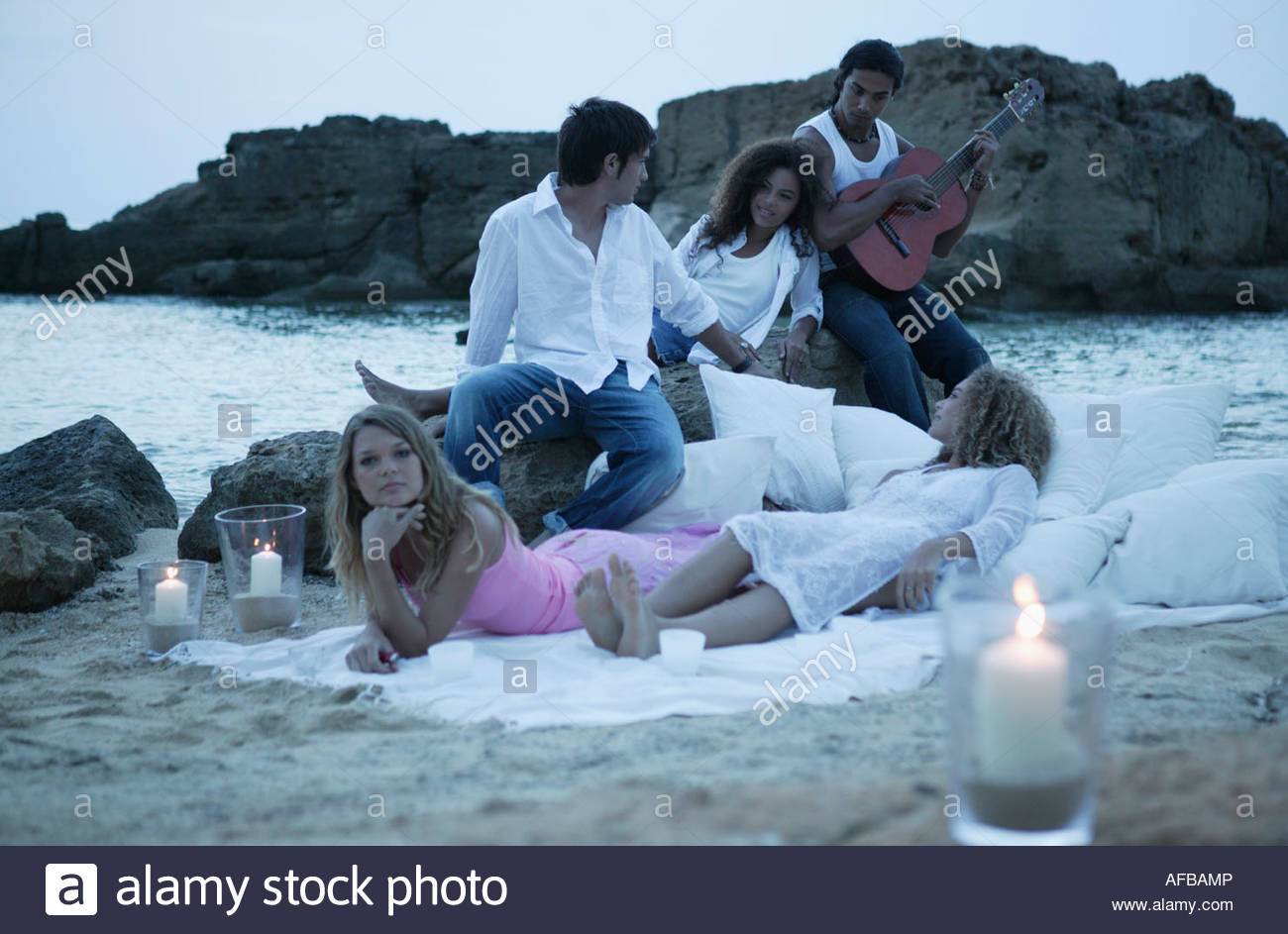 Two young men and three young women on the beach - Stock Image