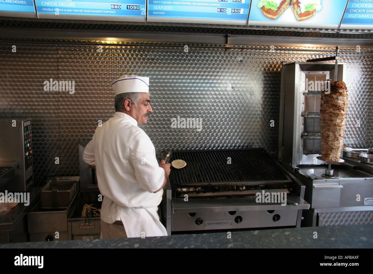 man preparing doner kebab in take-away restaurant - Stock Image