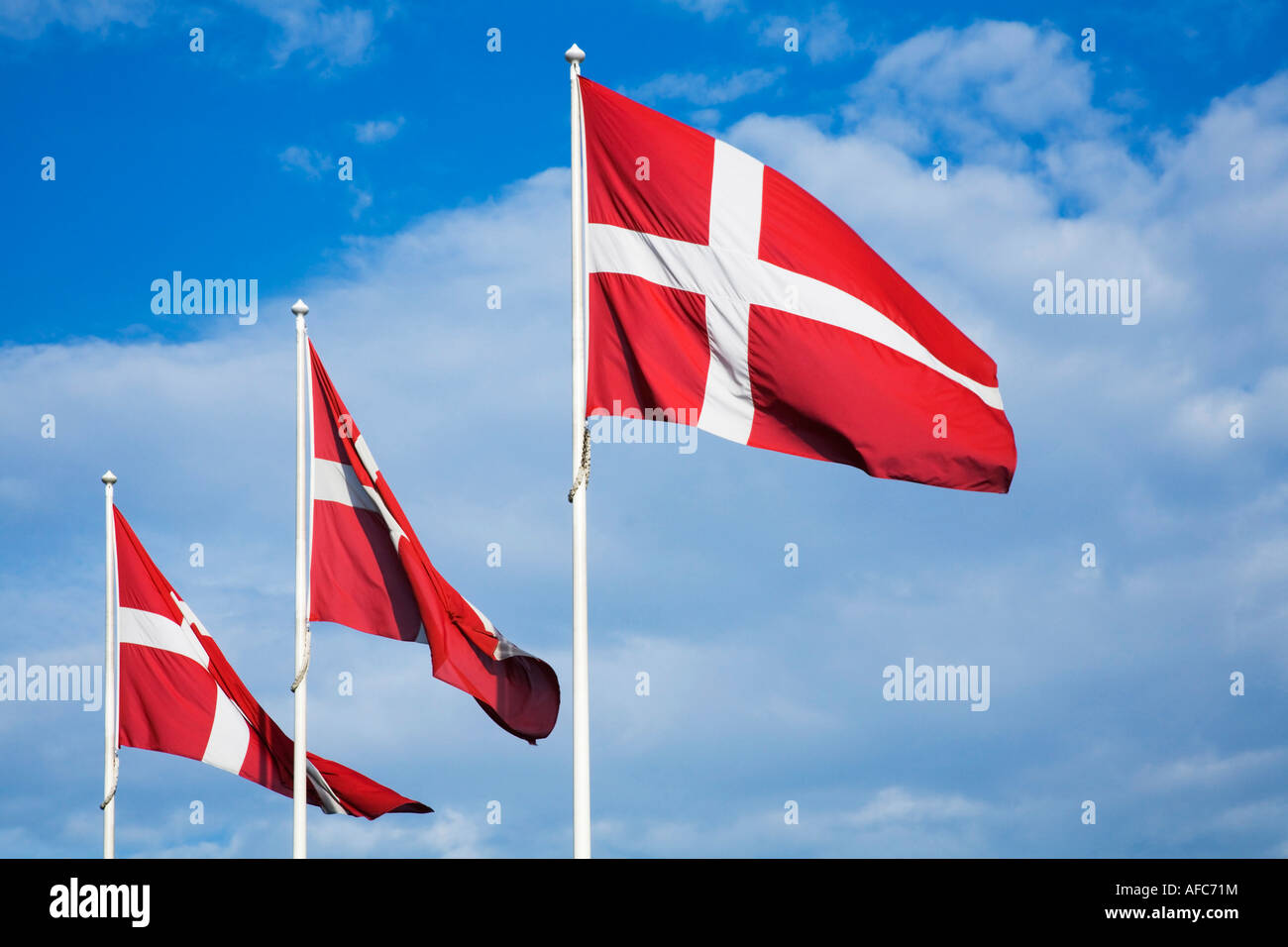 Danish Flags against a blue sky with clouds - Stock Image