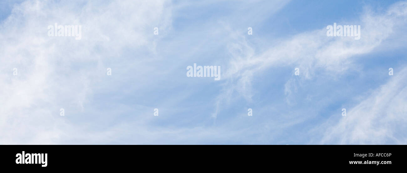 Panoramic of clouds in a clear blue sky - Stock Image