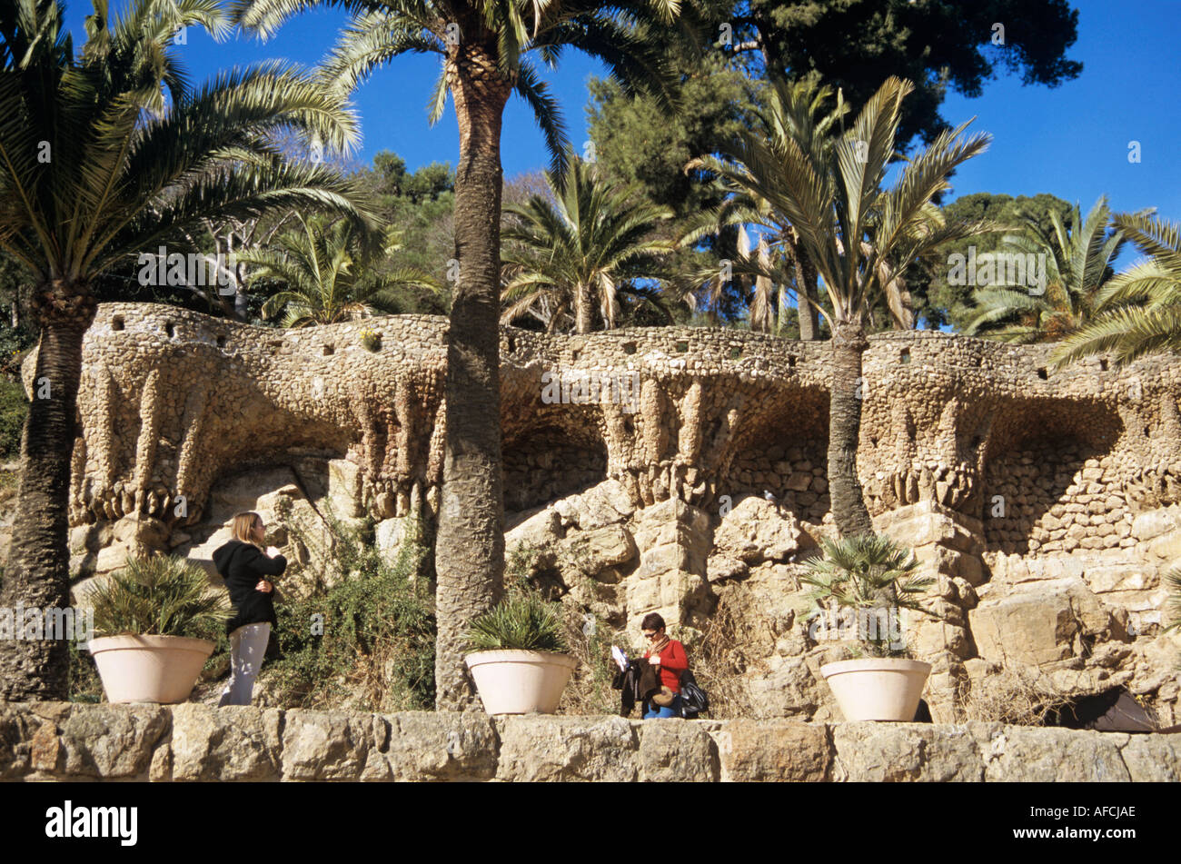 A distinctive walkway in Güell Park created by Antoni Gaudí in Barcelona overlooks a broad plaza - Stock Image