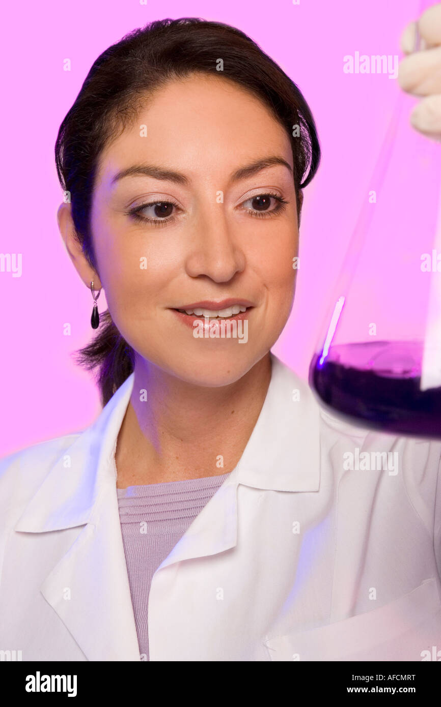 Science researcher checks fluid in beaker. - Stock Image
