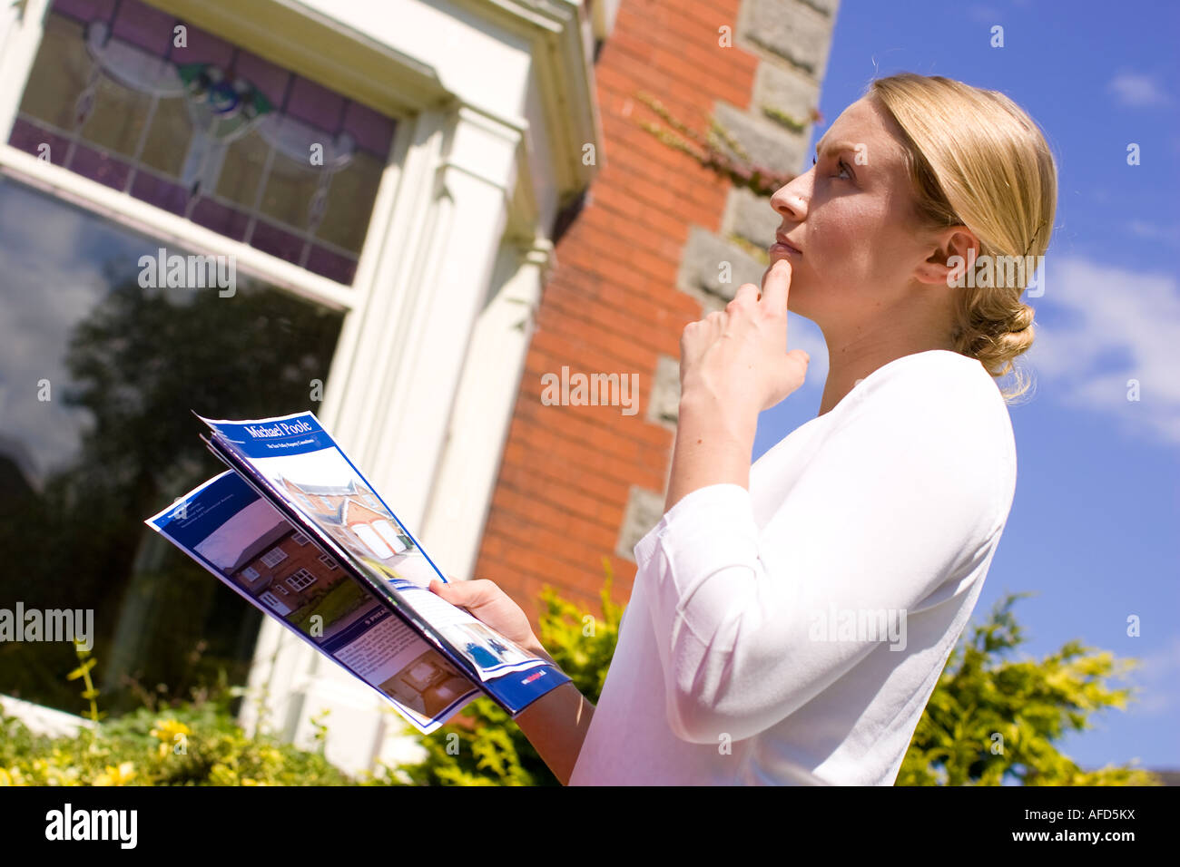 woman with details of a house standing outside it - Stock Image