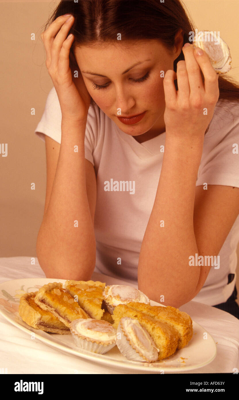 depressed woman looking at a pile of cakes - Stock Image