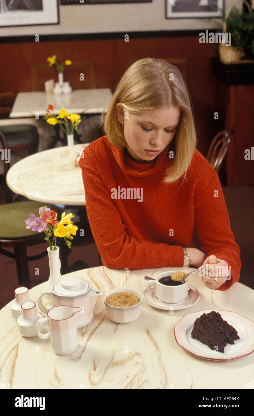woman looking moody putting sugar into her coffee - Stock Image