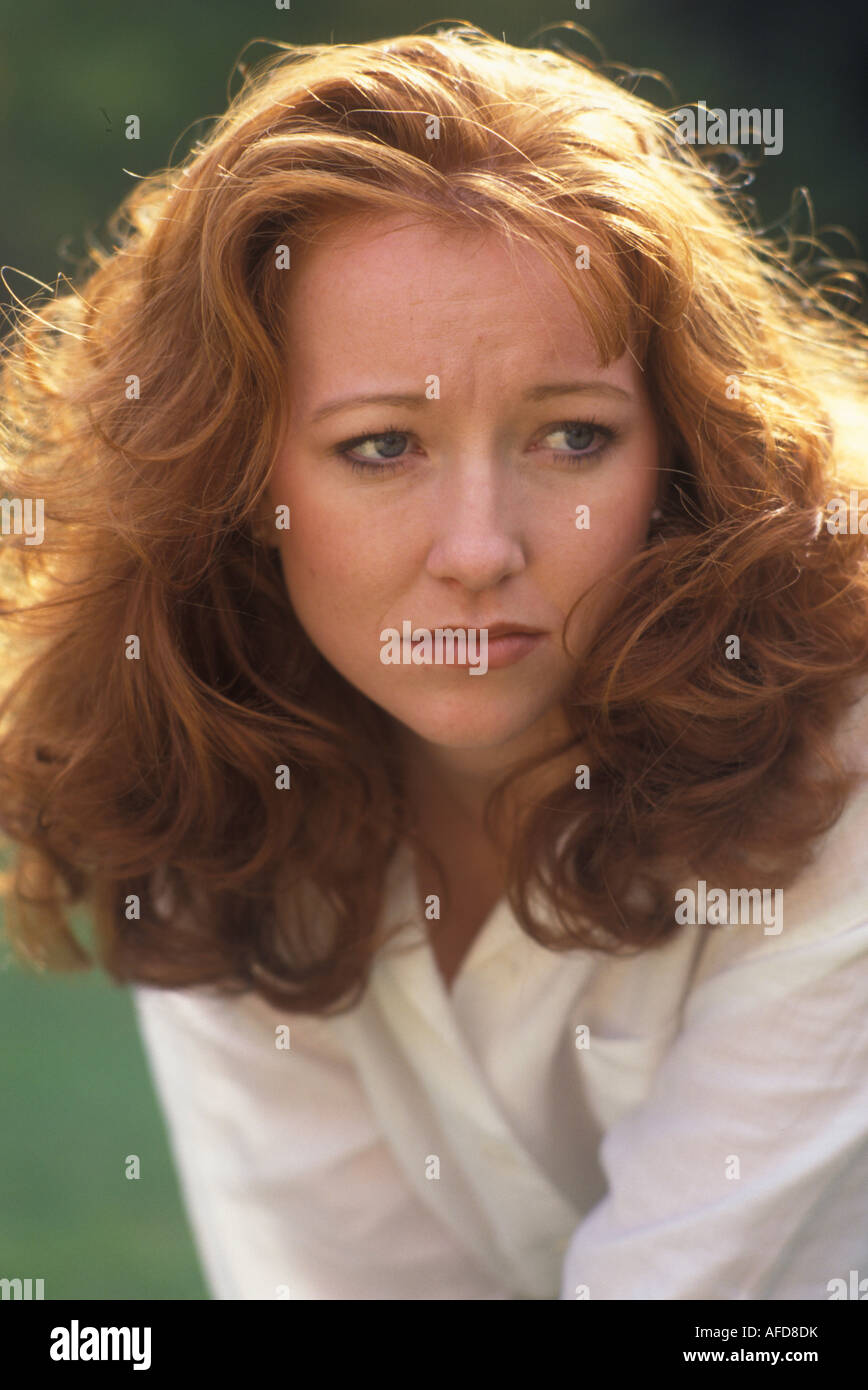 sad looking red headed woman - Stock Image