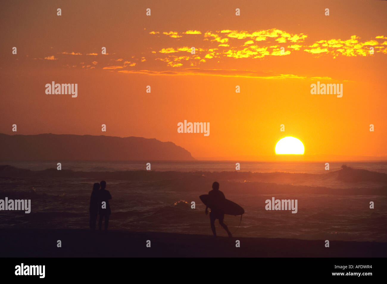 Couple & Surfer at Sunset, Barking Sands Beach, Polihale State Park, Kauai, Hawaii, USA Stock Photo