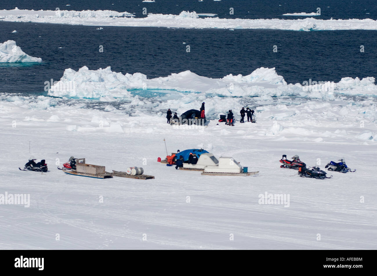 Snowmobile and sleds or qamotiqs plus zodiac  support diving film crew at the floe edge in the high Arctic. Disneynature - Stock Image